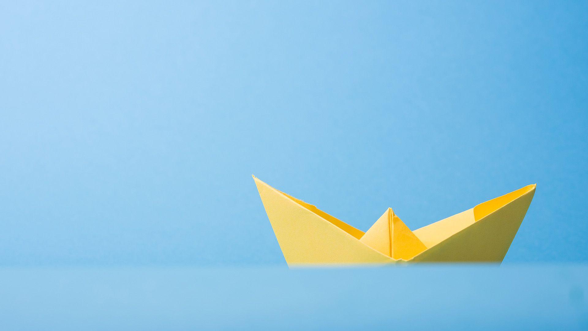 En gul papirbåt segler på det som er illustrert som blått hav og blå bakgrunn. Illustrasjon til sak om innholdsstrategi og kundereise for markedsføringsbyrået Elg.