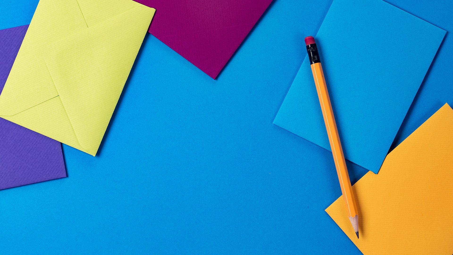 Fargerike konvolutter og en gråblyant som ligger på en blå bakgrunn. Illustrasjon til sak om innholdsstrategi for markedsføringsbyrået Elg.