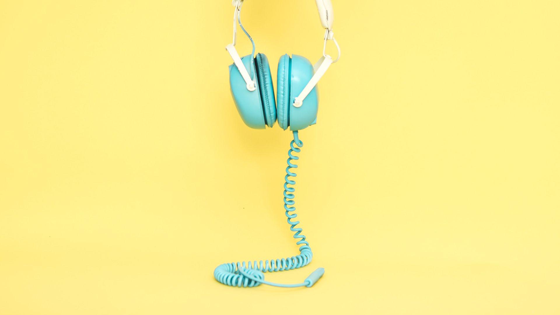 Turkise hodetelefoner på gul bakgrunn. Illustrasjon brukt til sak om sosiale medier for markedsføringsbyrået Elg