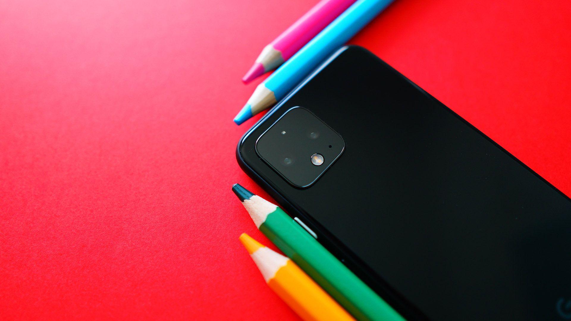 Sort mobil og fire fargestifter i oransje, grønn, blå og rosa ligger på en rød bakgrunn. Illustrasjon til sak om innholdsmarkedsføring for markedsføringsbyrået Elg.